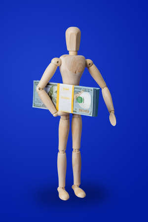 Wooden toy figure with money on blue background Zdjęcie Seryjne