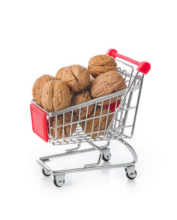 Walnuts in shopping cart isolated on white background Фото со стока