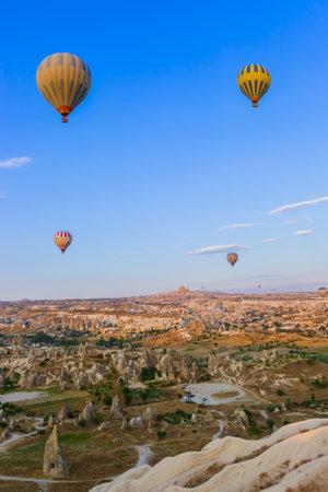 Cappadocia, Turkey - August 31, 2011: Hot air balloon flying over rocky landscape at sunrise in Cappadocia. Publikacyjne
