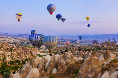 Cappadocia, Turkey - August 31, 2011: Hot air balloon flying over rocky landscape at sunrise in Cappadocia. Redactioneel