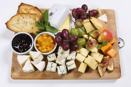 Arrangement of fruits and cheese on wooden board photo