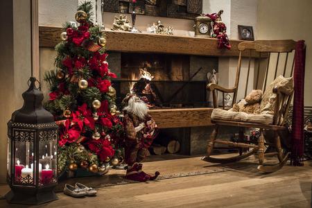 motivos navide�os: Interior de una casa rom�ntica adornada con el �rbol Chriastmas junto a chimenea de le�a y un sill�n de madera