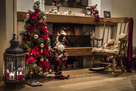 christmas tree presents: Romantic home interior decorated with Chriastmas tree next to burning fireplace and wooden armchair
