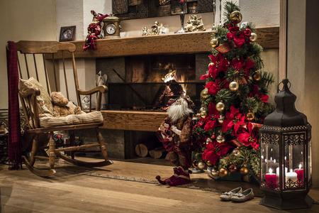 motivos navide�os: Ambiente acogedor de Navidad con el �rbol de Navidad decorado con adornos y cintas al lado de la chimenea ardiente Foto de archivo
