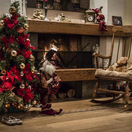 camino natale: Arredamento classico di albero di Natale con palline e nastri accanto al camino acceso