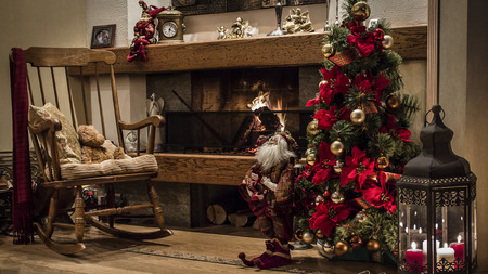 christmas  eve: Christmas tree decorated with baubles and ribbons next to fireplace and wooden chair in a house
