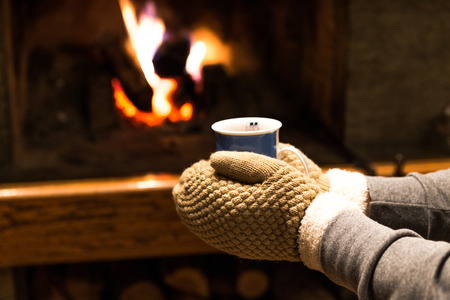Hands in gloves holding hot drink in front of fireplace at home photo
