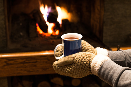 Two hands with gloves holding hot drink and fireplace background photo