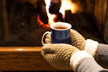 Hands with warm gloves holding blue cup of tea in front of fireplace at home photo