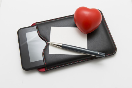 buss: Red heart with paper sheet and tablet om white background