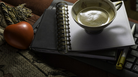 Closeup of cup of coffee, red heart, black diary and empty notebook with metallic spiral photo