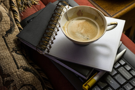 Cup of coffee with notebook and black keyboard on furniture at home photo