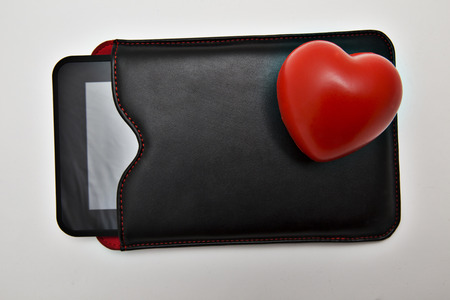 buss: Closeup of tablet in leather case and cute little red heart Stock Photo