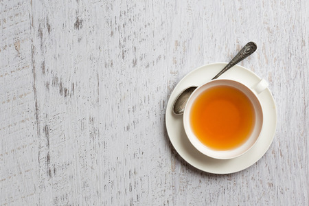 drinking of tea: White china cup of tea on vintage white wooden background