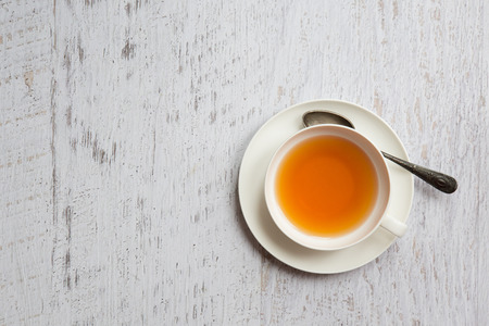 tea break: White cup of tea with metallic spoon on vintage white background, top view point