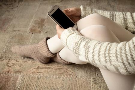 cross legged: Cross legged woman holding smartphone