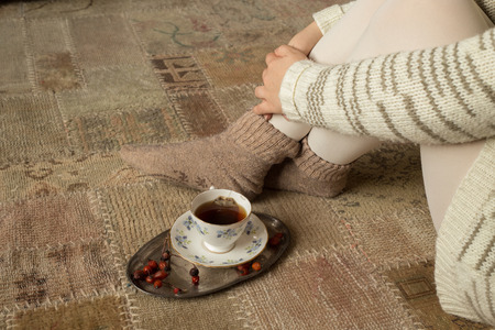 chillout: Cup of herbal tea on carpet and crossed woman legs Stock Photo