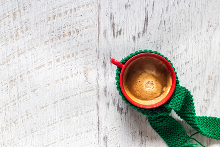 Red cup of coffee wrapped with green scarf on white wooden background