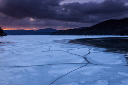 Frozen lake and the dark clouds, winter landscape photo