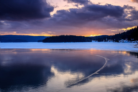 Cold lake in the winter during sunset photo