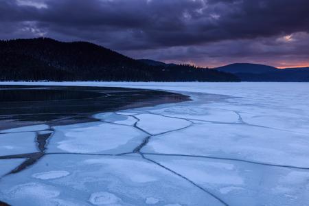 Creaking ice of frozen lake in the mountain photo