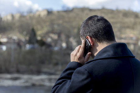 oudoors: Rear view of man talking on his mobile phone
