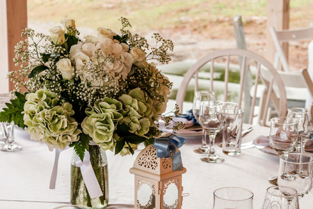 celebration event: Fresh flowers in glass vase on a table decorated for event Stock Photo