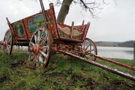 carreta madera: Viejo vagón de madera ornamentada abandonada junto a un árbol