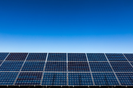 solar collector: Row of solar panels and clear blue sky background