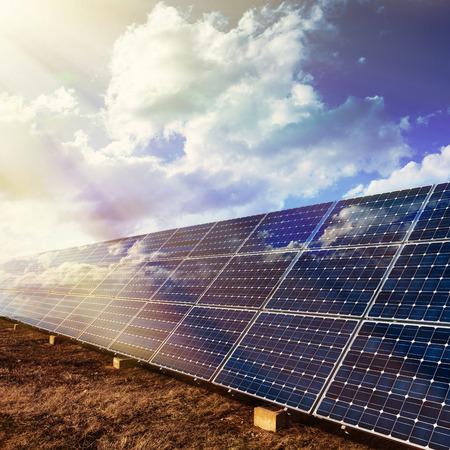 paneles solares: Fila de los paneles solares fotovoltaicos y cielo nublado de fondo