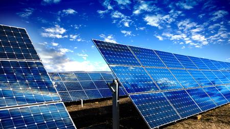 paneles solares: Las filas de paneles solares fotovoltaicos y cielo azul con nubes Foto de archivo