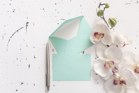 Blue envelopes and pen decorated with orchid flower