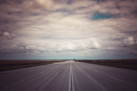 forthcoming: Wide road goes the distance under dramatic cloudy sky