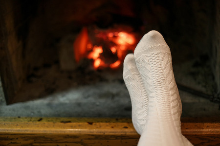 fireplace home: Feet in wool white colored knitted socks warming at the fireplace