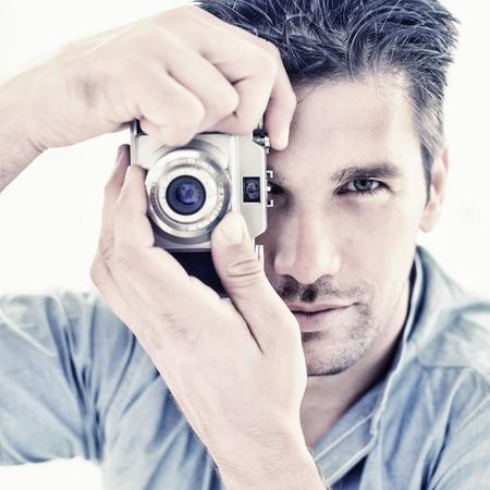 attractive male: Portrait of attractive male photographer staring at vintage camera Foto de archivo