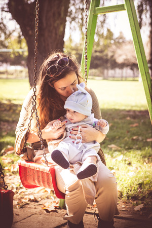 Young mother kissing her baby boy outside the park