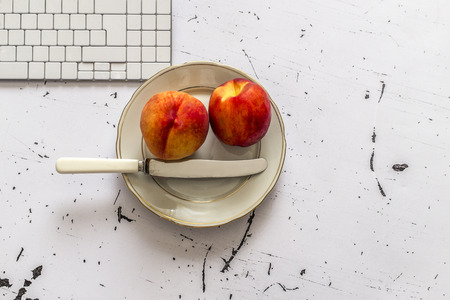 quick snack: Two peaches and table knife in plate on the office table Stock Photo