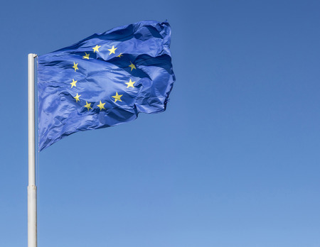 blown: Wind blown blue colored european union flag and clear sky background