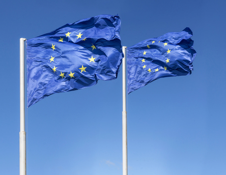 blowed: Closeup of wind blowed pair of european union flags Stock Photo