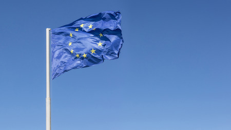 blown: Wind blown european union flag against blue sky background