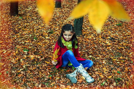 ouside: Beautiful young girl sitting on fallen dry leaves in the woods
