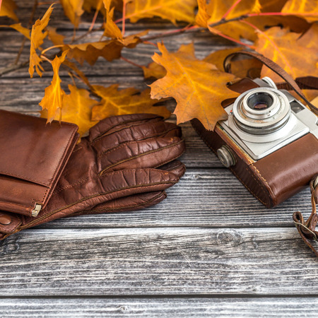 autumn grunge: Closeup of retro camera with clothing accessories over wooden background Stock Photo