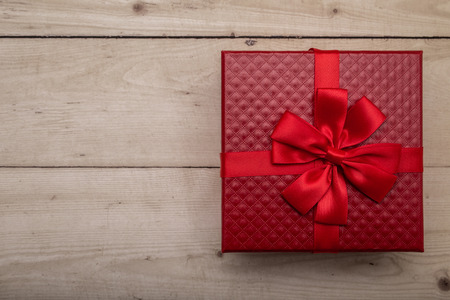 Top view of red leather gift box on vintage wooden background