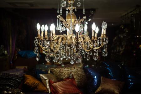 illuminating: Closeup of ornamented gold chandelier illuminating living room Stock Photo