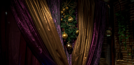 lighted: Closeup of lighted christmas decoration on gold and purple luxury curtains
