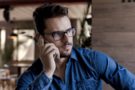 looking aside: Front view of handsome model man holding smartphone and looking aside Stock Photo