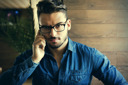 inteligent: Handsome male with blue shirt and eyeglasses using smartphone, closeup portrait