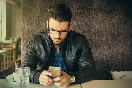 modelos hombres: hombre guapo con gafas y chaqueta de cuero que usa smartphone