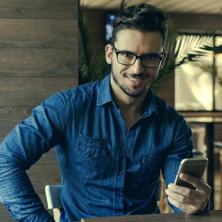 inteligent: Portrait of modern man with elegant haircut using mobile phone