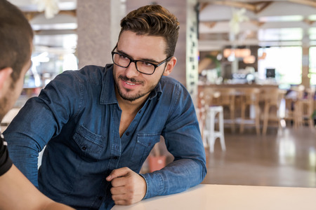 inteligent: Handsome man with blue shirt and eyeglasses sitting on table